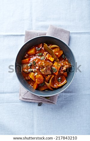 Beef and squash goulash topped with pumpkin seeds (autumn style) - stock photo