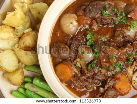 Beef bourguignon stew with fork-crushed new potatoes and asparagus. - stock photo