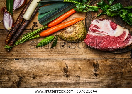 Beef brisket with vegetables ingredients for soup or broth cooking on rustic wooden background, top view, border - stock photo