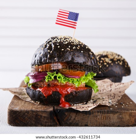 Beef burger with a black bun; with lettuce and mayonnaise and ketchup ...