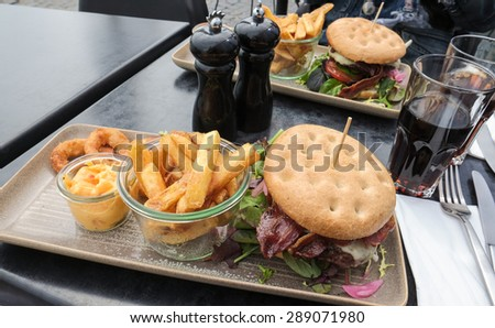 Beef burger with bacon, french fries and onion rings on a long square plate - stock photo