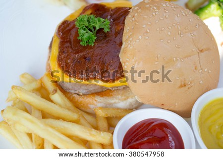 Beef burger with cheddar cheese and sauce.
