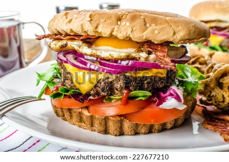 Beef burger with red onion and fried egg, crispy bacon and salad, onion bhajis - stock photo