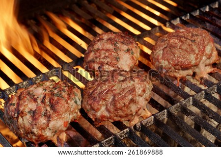 Beef Burgers On The Barbecue Grill. Charcoal Flames On the Background.