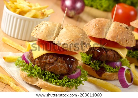 Beef burgers with cheese and vegetables.Selective focus on the front burger - stock photo