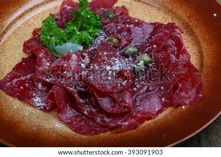 Beef carpaccio with cheeese and parsley leaves