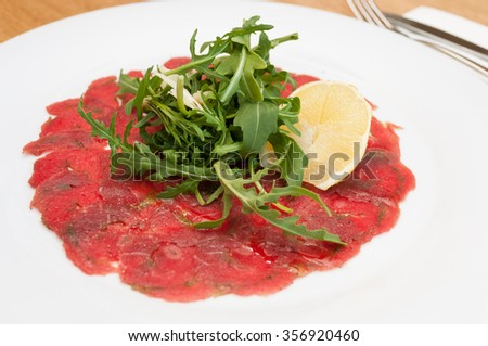 Beef Carpaccio with Parmesan Cheese, Lemon and Wild Rocket - Shallow Depth of Field - stock photo