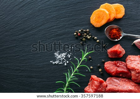 Beef casserole / goulash ingredients on black slate background viewed from the top - stock photo