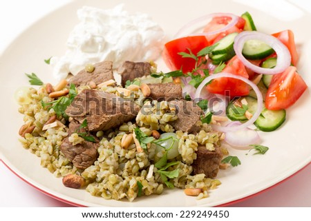 Beef, cooked with onion and spices and served on a bed of frikeh,with a salad and yoghurt and garnished with nuts. - stock photo
