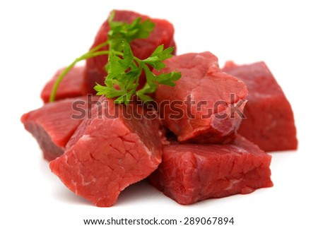 beef cubes with parsley on white background  - stock photo