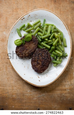 Beef cutlets with beans, rustic wooden background, view from above