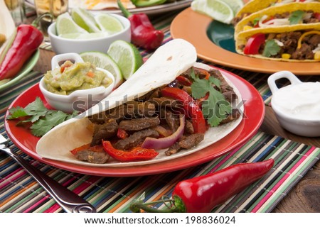 Beef fajitas as the main subject with assorted Mexican dishes around.  - stock photo