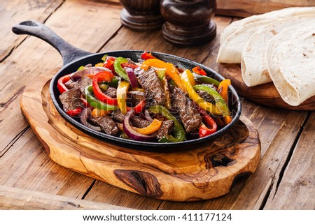 Beef Fajitas with colorful bell peppers in pan and tortilla bread - stock photo