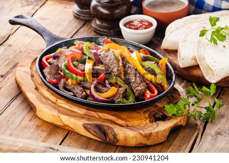 Beef Fajitas with colorful bell peppers in pan and tortilla bread and sauces - stock photo