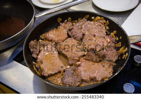 Beef flank steaks with sauce on pan - stock photo