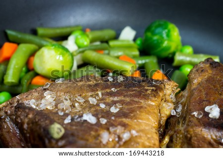 Beef fried with vegetables in a pan close-up with selective focus