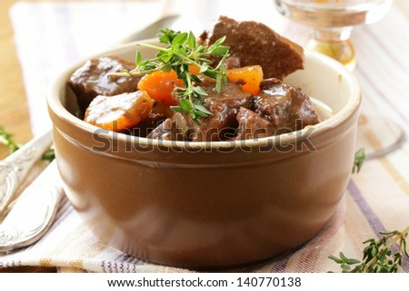 beef goulash (stew)  with vegetables and herbs on a wooden table - stock photo