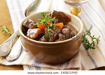 beef goulash (stew)  with vegetables and herbs on a wooden table