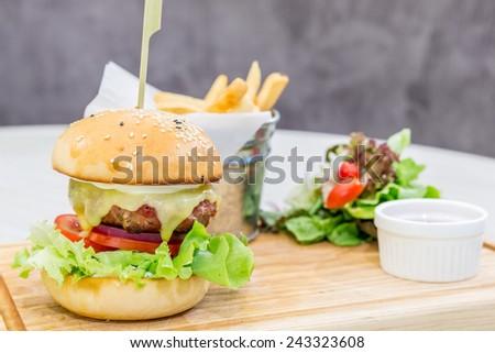 Beef hamburger cheese on wooden dish - stock photo
