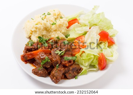 Beef in red sauce with a salad and mashed potato - stock photo