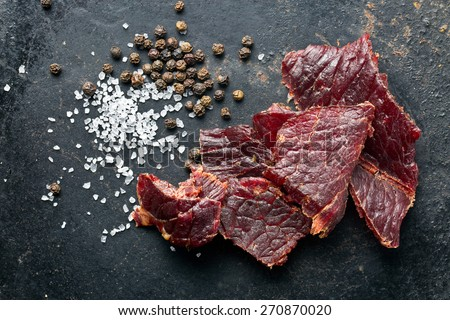 beef jerky and spice on old table - stock photo