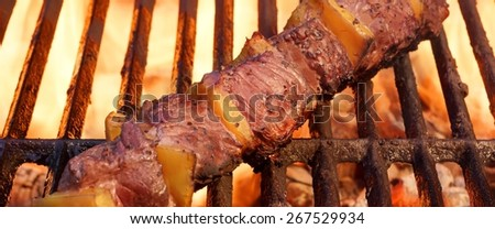 Beef Kebab or Shashlik On The Hot Barbecue Grill Closeup. Flaming  Charcoal Grill In The Background. Meat Food For Weekend  BBQ or Picnic Party. - stock photo