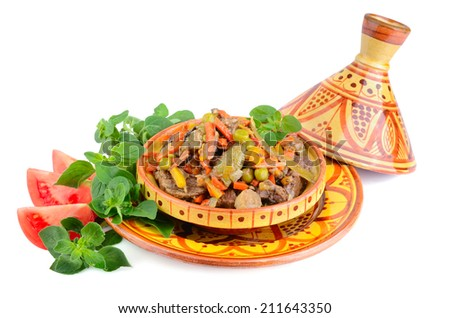 Beef meat and vegetables in moroccan national dish tajine with marjoram and tomatoes on a white background
