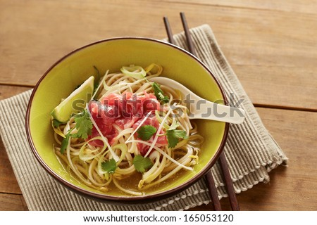 Beef meat rice noodle pho soup on wooden table