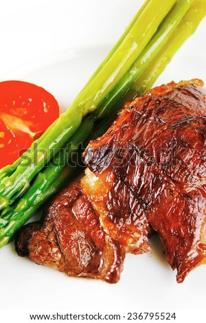 beef meat served with asparagus on white dish - stock photo