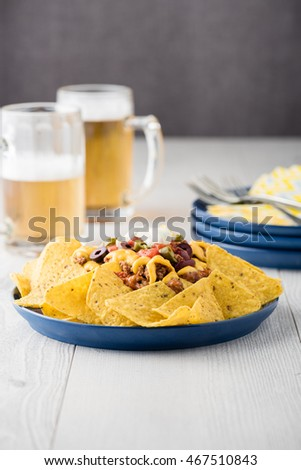 Beef nachos with beers on rustic background