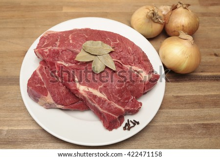 Beef on a plate with a few onions - stock photo