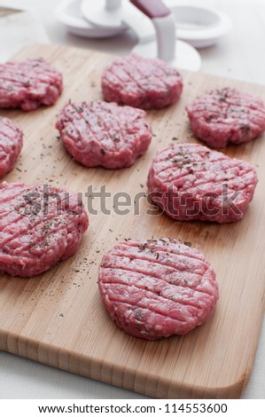 Beef patties with pounder uncooked vertical - stock photo