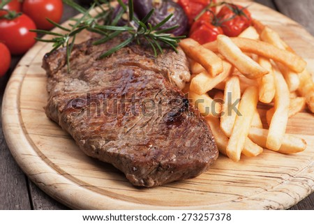 Beef rib-eye steak with french fries on wooden board - stock photo