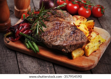 Beef rib-eye steak with roasted potato and vegetables - stock photo