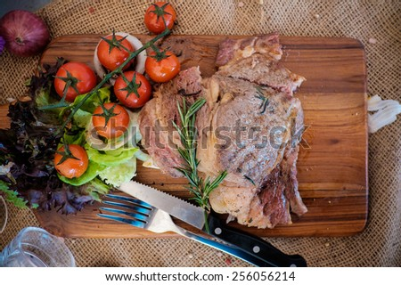 Beef ribeye steak with knife and fork for meat on cutting board  - stock photo
