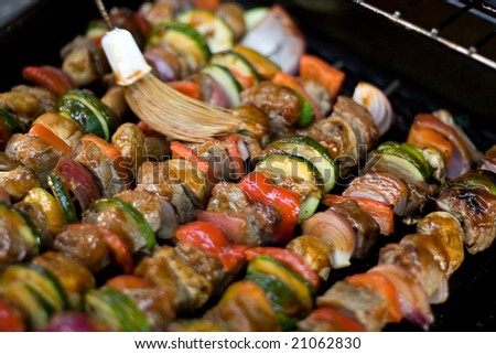 Beef shish kebabs on skewers, cooking on the grill.  Shallow depth of field. - stock photo