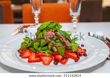 Beef sirloin served with arugula, lamb's lettuce, pomegranate and strawberries drizzled with a fruit dressing. - stock photo