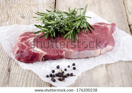 beef sirloin steak with rosemary on kitchen paper - stock photo