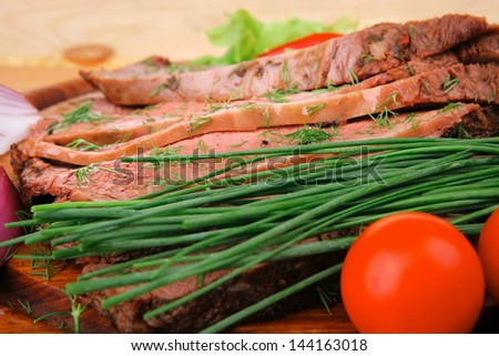 beef slices on plate with vegetables over wooden table