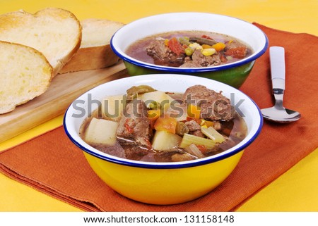 beef soup served with buttered toasted crusty italian bread. Soup ingredients are potatoes, mixed vegetables, low sodium beef broth, onions, celery, garlic and various herbs and spices. - stock photo