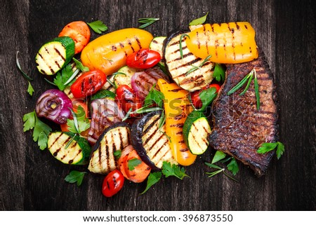 Beef steak and Grilled vegetables. On cutting dark board background - stock photo