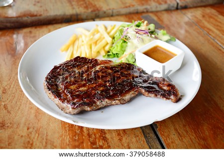 beef steak and recipe dish on wooden table - stock photo