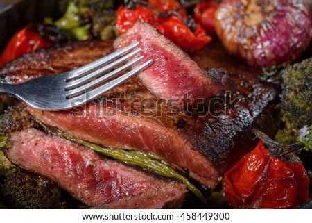 Beef steak medium rare with grilled vegetables in a pan. a piece of meat strung on a fork. still life of food in low key style rustic - stock photo