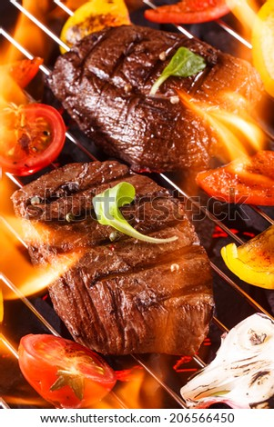 Beef steak on a barbecue grill with flames with vegetables - stock photo