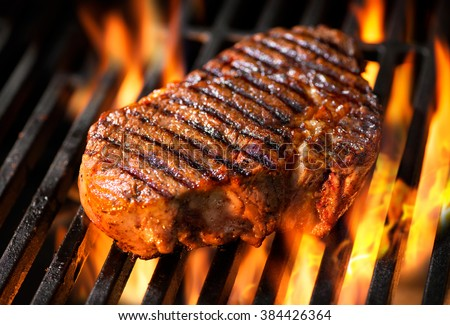 Beef steak on the grill with flames - stock photo