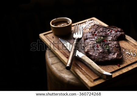 Beef steak. Piece of  Grilled BBQ beef marinated in spices and herbs on a rustic wooden board over rough wooden desk with a copy space. Top view. Stock Image - stock photo