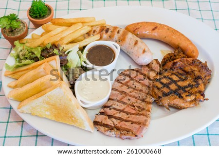 Beef steak serve with french fries, sausage, grill bread and gravy sauces.  - stock photo