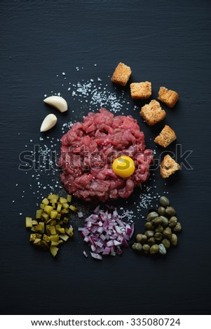 Beef steak tartare over black wooden surface, above view
