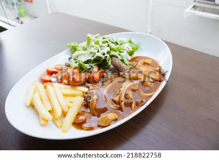 Beef steak topped with sauce on a white plate - stock photo