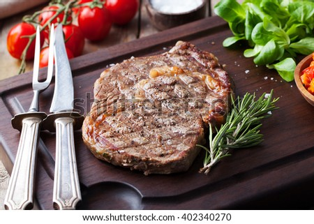 Beef steak with cherry tomato and rosemary on a dark cutting board Wooden background Copy space - stock photo